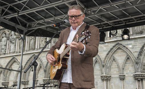 En enkel kassegitar har vært viktig i Ivar Skippervolds brobyggerarbeid, som han ble hedret for under Olavsfestdagene foran vestfronten av Nidarosdomen i sommer. Foto: Marianne Lystrup