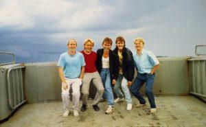 Geirmund Engevik, Steinar Raunholm, Kjell Magnar Helland, Heine Helland og Tore Vik. På veg til spelejobb på Bakkasund, 1986. Fitjargutane måtte ta tre ferjer kvar veg. Bilete er teke ombord på ferja mellom Hufthamar og Hundvåkøy med sjølvutløyser.