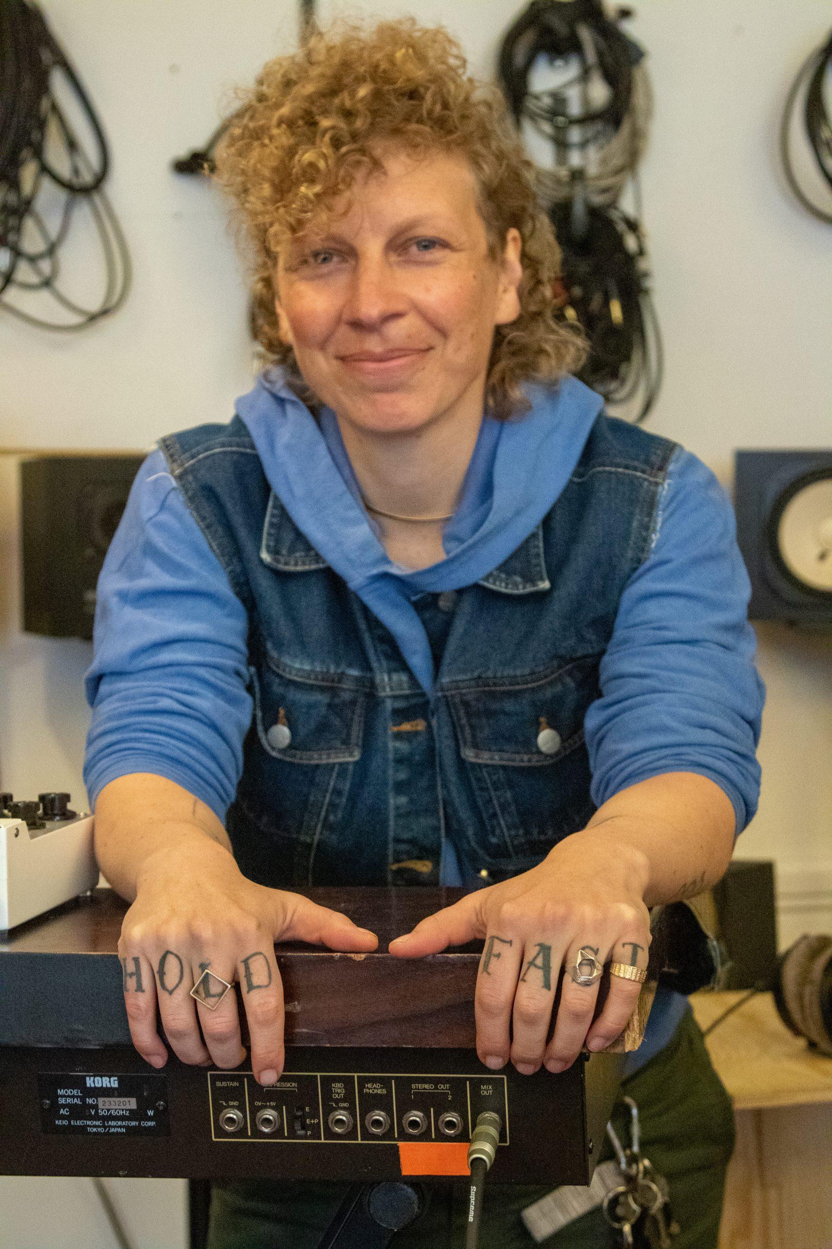 Blond kvinne, stående, tatoverte hender holder rundt en mikser