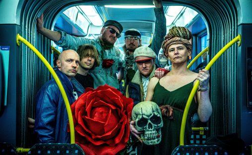 Fem personer står i en trikk, en holder en enorm rød rose, en person holder en stor hodeskalle, en person i grønn stroppekjole og dreds, fire personer i ytterjakker, tre med capser/sixpence og solbriller